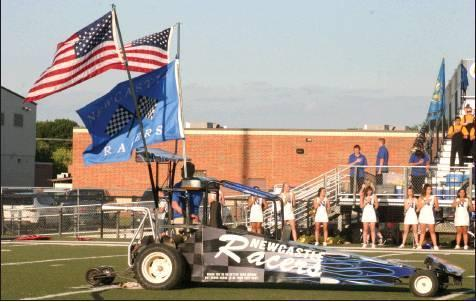 ›Todd Newville/The Newcastle Pacer                                The symbolic Racers car sits as the National Anthem is played before the Newcastle and Noble football game.